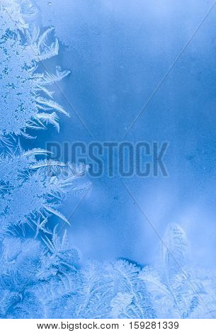 Slightly blurred beautiful frost pattern on a window glass (with copy space for your text) abstract winter background
