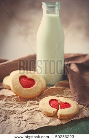 Cookies with milk and parchment on table, closeup