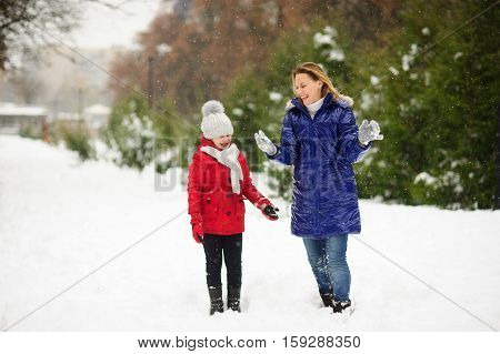 Young woman with the daughter on walk in winter day. Woman and the girl are dressed in bright down-padded coats. Woman without headdress. It is snowing. All ground in the park is covered with snow.