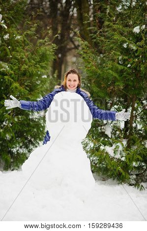 White Christmas. Cute young woman builds a big snowman in the park. To her it is very cheerful. The woman without headdress. It is snowing. All ground in the park is covered with snow.