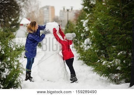 The young woman and her daughter build a snowman. They establish the head to a big snowman. In the park it is snowing snowdrifts lie. Mother and the daughter cheerfully spend time.