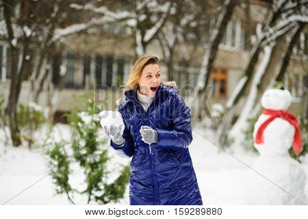 Young woman plays snowballs. It is snowing. Earth is covered with snowdrifts. Woman is dressed in blue warm jacket without headdress. Excited by play she does not feel cold. Nearby there is snowman.