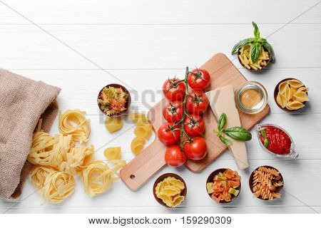 Different kinds of pasta and tomatoes on wooden background