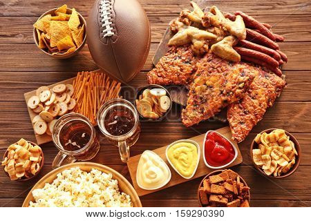 Table full of tasty snacks and beer prepared for watching rugby on TV