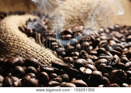 Fresh coffee beans with smoke on sackcloth background