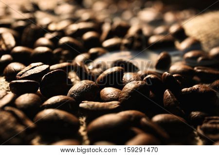 Fresh coffee beans on sackcloth background