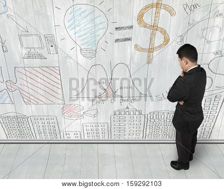Man Looking At Business Concept Doodles On Wooden Wall