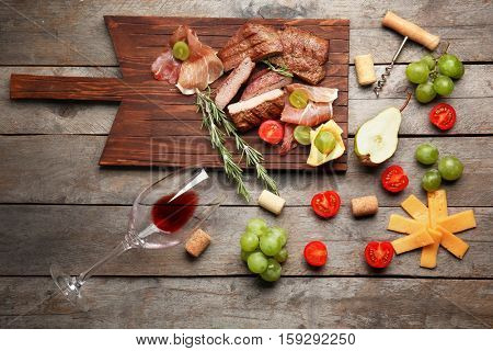 Grilled steak and appetizers with wine on wooden table
