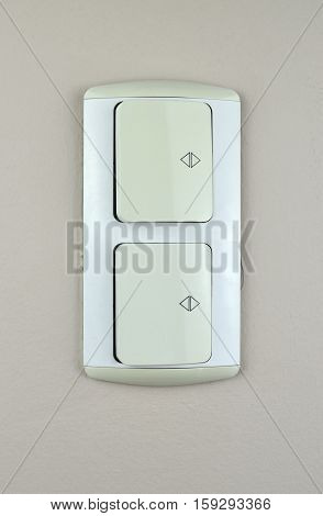 Two white switch plugs on a beige wall