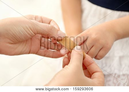 Woman wrapping sticking plaster around little girl's finger, close up view