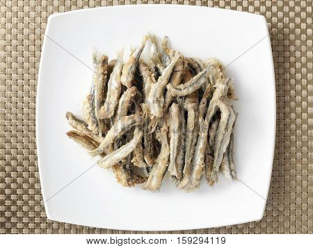 Anchovies in breadcrumbs and fried in oil. Cooked and ready. Italian culinary specialties. View from above