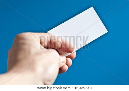 Hand Holding An Empty Business Card On Blue Background