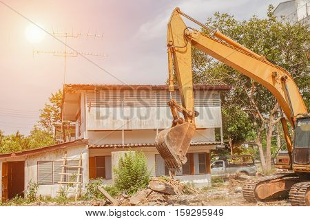 bucket excavator destruction in work outdoor construction with sunset light tone