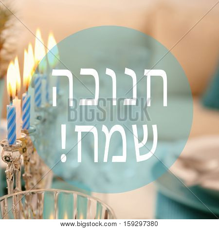 Menorah with candles on table served for Hanukkah celebration. Text HAPPY HANUKKAH in Hebrew