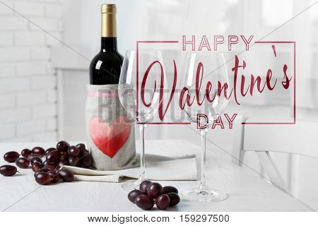 Text HAPPY VALENTINE'S DAY. Glasses and bottle of red wine on table.