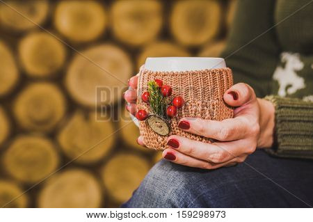 Cup of hot tea or coffee or cocoa in knitted vintage cup holder with christmas decorations in hands of woman with beautiful festive red manicure. Woman sitting in rustic interior. Horizontal photo