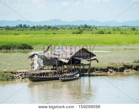 Very simple traditional farmhouse made from straw but with a solar panel on the roof for electricity along the Kaladan River in the Rakhine State of Myanmar.