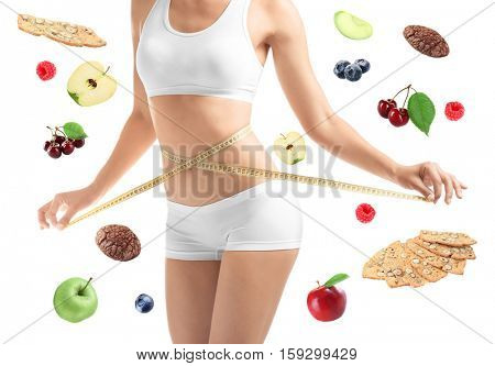 Woman with measuring tape around waist and healthy food on white background. Diet and fitness concept.