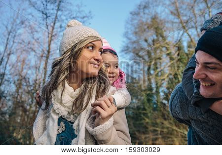 Portrait of smiling woman giving piggyback ride to happy little girl next to man holding kid into the forest