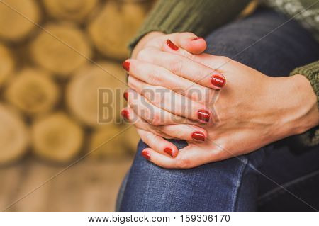 Woman sitting indoors with her hands crossed on knee. Young woman wears green sweater and blue denim jeans. Fingernails with beautiful fresh red manicure. Close up horizontal color photo.