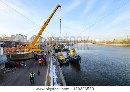 MOSCOW, RUSSIA - NOVEMBER 11, 2016: State Unitary Enterprise Mosvodostok performs recovery vessels on coastal winter parking. Truck Crane prepares to lift the ship.