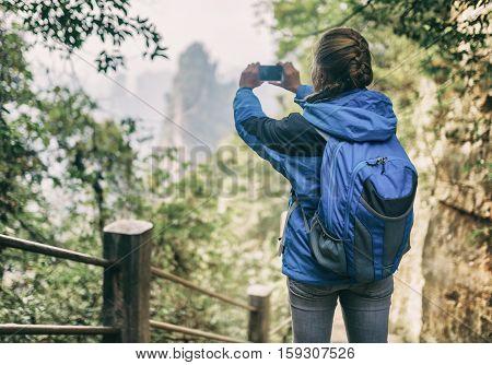 Female Tourist Taking Photo Of Scenic Mountain. Toned Image