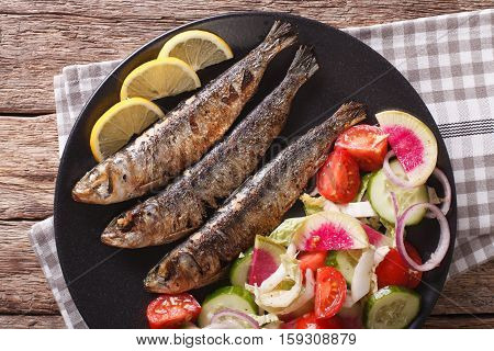 Grilled Sardines With A Salad Of Cucumber, Radish, Tomato, Onion Close-up. Horizontal Top View