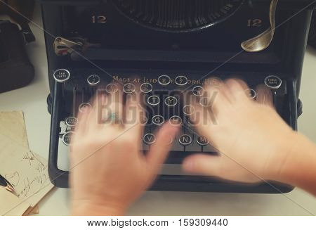 Someones hands typing on black vintage typewriter, top view, retro toned