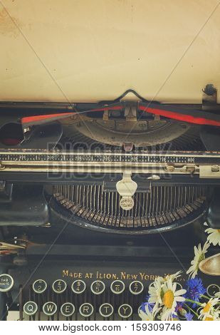 black vintage typewriter and antique paper with copy space, retro toned