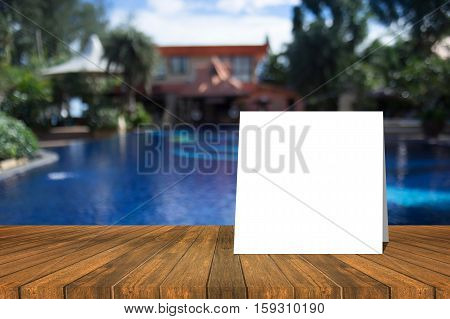 White Card Put On Wood Table And Beautiful View Of Swiming Pool At Resort In Background. Product Dis