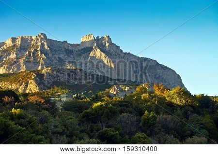Mount Ai-Petri Krypno Pan. At the foot of the mountain is a forest or park. In the forest, lit by sunlight, it is an ancient palace and fortress with towers. Sunny day. Blue cloudless sky.
