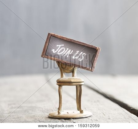 The words JOIN US and golden chair on the wooden background