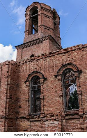 A ruined church. Part of brick wall and bell tower on blue sky background. The photo was taken in Russia in Ugol'noye village in August 2015.