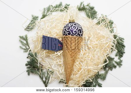Colorful Christmas or New Year decoration with purple silver christmas ball ice cream cone blue tag with rose thread and tree branch on white background
