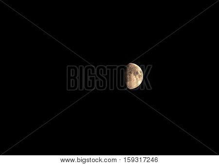 View of a partial moon in the night sky.