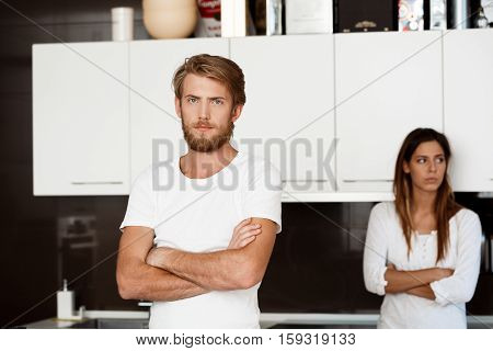 Displeased handsome man in quarrel with his girlfriend background at home.