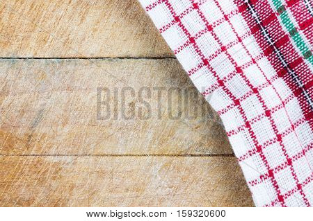 Christmas colored kitchen towel on old rugged natural wooden cutting board. Flat lay top view. Copy space at the bottom left corner.