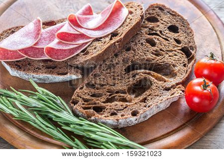 Sandwiches with dark-rye bread and salami on the wooden board