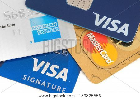 Close up on credit cards with Visa,MasterCard and American Express logos on white background,illustrative editorial