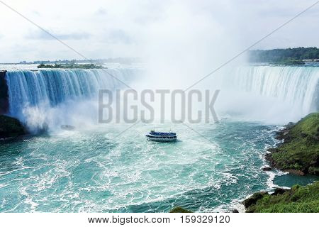 ferry in ocean next to big waterfall