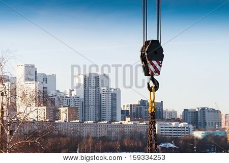 Hook suspension crane on the background of high-rise buildings. Abstract industrial background.