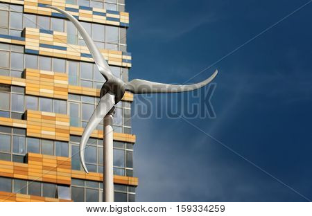 Small Wind Turbine In Front Of A Modern Building