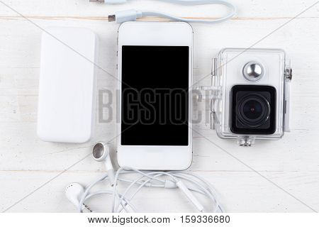 White technology on natural wooden table background. Smart phone power bank cable headphones action camera. Flat lay top view.