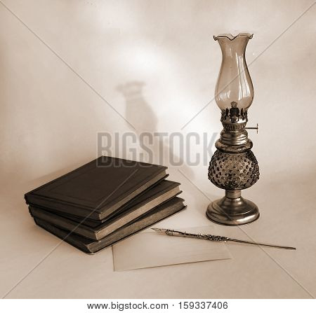 Blank paper card oil lamp and inkwell with dip pen as a concept of writing letters and greetings on holidays. Photo in sepia tone