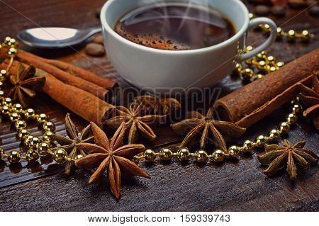 A cup of hot coffee star anise and cinnamon sticks among festive tinsel. Aromas holiday. Home comfort. Christmas atmosphere. Morning.Close-up.