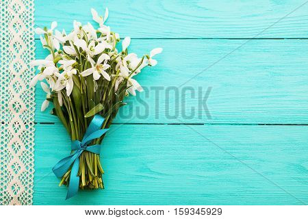 Wedding day. Fresh bouquet of flowers and lace ribbon on blue wooden background. Top view