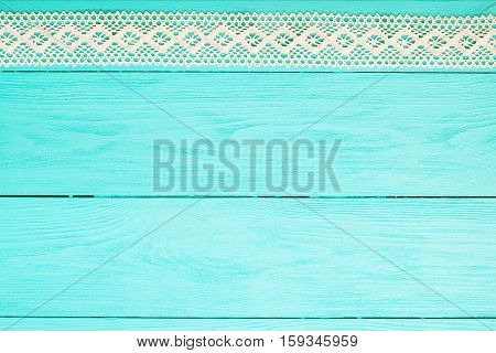 Lace bow on blue wooden background. Top view and copy space.