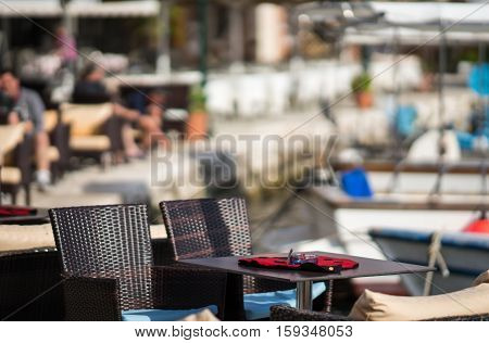 Table And Cloth In The Form Of A Ladybug On A Blurred Background Of The City And Port Of Fiskardo, K