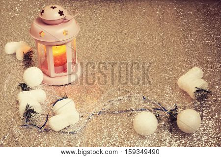 Vintage lantern with burning candle stands on a silver background surrounded by Christmas-tree decorations and garlands. Preparing for Christmas. Copy space. Top view.