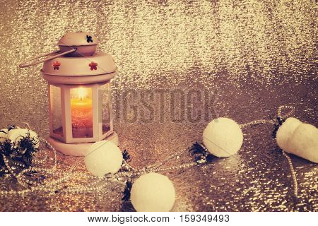 Old lantern with burning candle stands on a silver background surrounded by Christmas-tree decorations and garlands. Preparing for Christmas. Copy space.